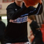 Before the game, senior Will Curran warms up by shooting free throws. Photo by Reilly Moreland