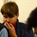 Senior Daniel Bond covers his nose due to the pungent smell within one of the treatment buildings. Photo by Luke Hoffman