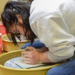 Junior Jia Self carefully starts works on centering her clay. Photo by Kathleen Deedy