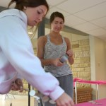 Sophomores Caroline Chisholm and Anna Parker set up the entry table by the door where students will be admitted to the dance. Photo by Luke Hoffman