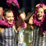 Sophomores Claire Baker and Lauren Dierks play with their boas before performing at half time.  Photo by Evelyn Roesner