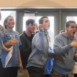 SM East swim team members and supporters cheer on sophomore Andrew Fey as he takes fourth place in his 100-yard backstroke event. Photo by Luke Hoffman
