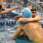 After their race, junior Walter Honnold and sophomore Kaleb Hagg embrace after their final race of the swim season. Photo by Luke Hoffman