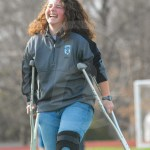 Sophomore Sophie Rice laughs as she crosses the field on crutches. Photo by Annakate Dilks