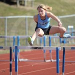 During her event, junior Aislinn Menke jumps over a hurdle. Photo by Reilly Moreland