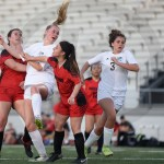 Junior Camryn Gossick heads the ball towards the goal as sophomore Sydney Herpich runs after it. Photo by Aislinn Menke