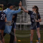 Junior Kelly Brackin gives Coach Ehrich a high five after she cut across the field and scored. Photo by Noelle Griffin