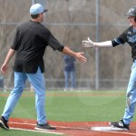 After senior Daniel Hammond runs to first base, coach Ben Calvano high fives him. Photo by Julia Percy