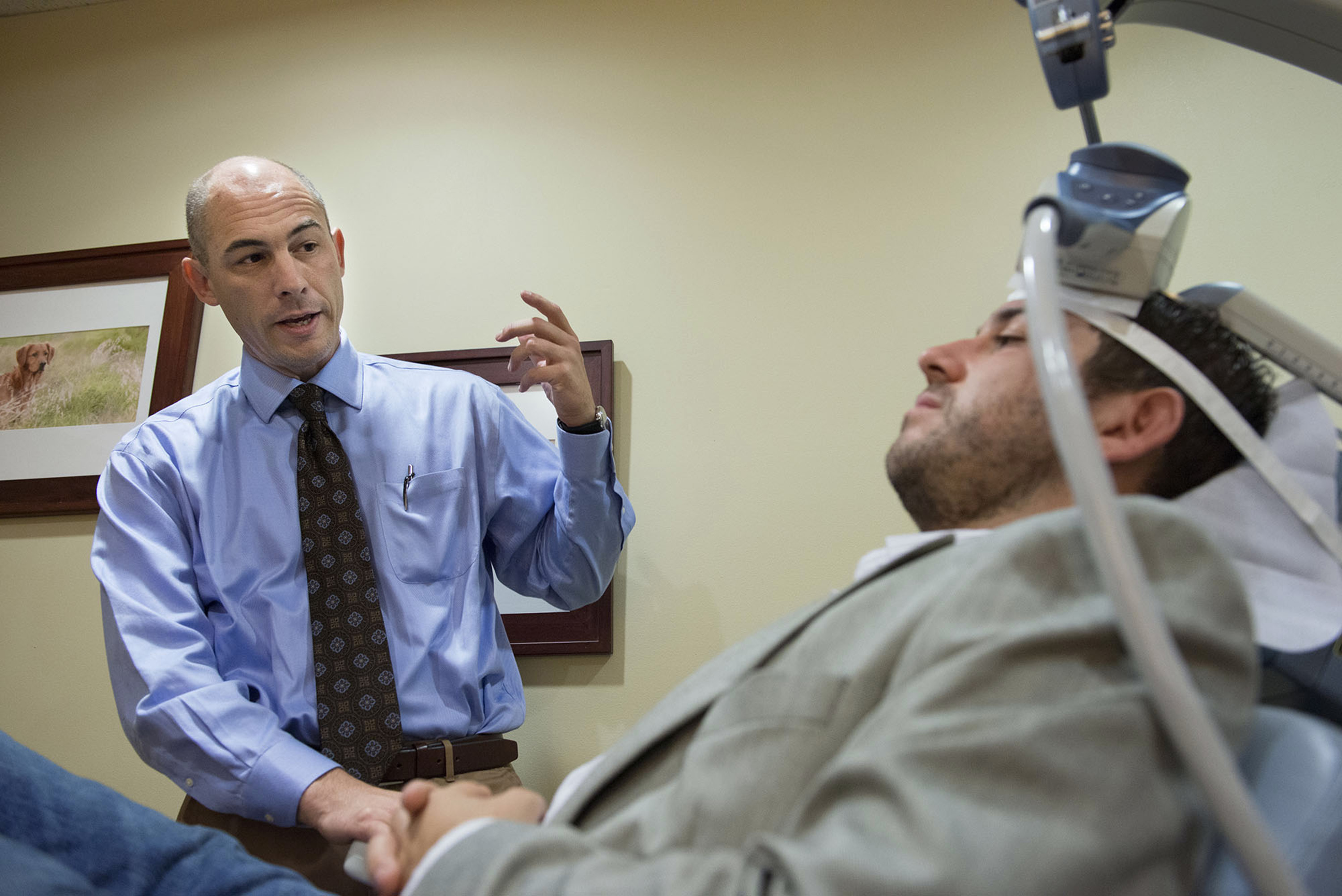 Dr. Richard Bermudes talks to his patient, 31-year-old Nicholas O'Madden, who suffers from anxiety and depression and receives treatment with Transcranial Magnetic Stimulation (TMS) therapy, which uses a large magnet to stimulate certain parts of the brain to alleviate depressive symptoms at TMS Health Solutions on July 2, 2015 in Sacramento, Calif. (Randy Pench/Sacramento Bee/TNS)