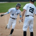 Junior John Weedman goes to high five head coach Gordon after scoring the first run of the game. Photo by Sarah Golder