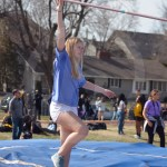 Sophomore Jane Ford lifts the bar knocked over by a practicing pole vaulter. Many of the jv track members, like Jane, worked the track meet to help keep things efficient and in order. Photo by Taylor Keal