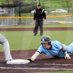 Getting a big lead off of first base, sophomore Ben Beikmann slides back into first base after being back picked by the Rockhurst pitcher. Photo by Megan Biles