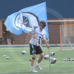 Sophomore Cade Eldred takes the East flag out onto the field. Photo by Noelle Griffin