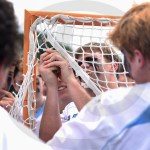 Senior Joseph Mohr cuts a piece of the goal to keep after their win. Photo Julia Percy