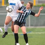Junior Cate Nearmyer jumps up to gain control of the ball. Photo by Luke Hoffman