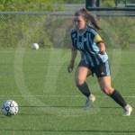 Senior Emily Cooper runs toward the ball to then pass to a teammate. Photo by Elle Karras
