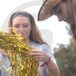 Sophomore Sadie Mcdonald admires the gold streamers as she unravels them in preparation for putting them on the float. Photo by Morgan Woods