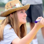 "Sophomore Sadie McDonald makes a sign to put on the side of the float saying, ""Yee Haw Lancers"". Photo by Bella Wolfe"