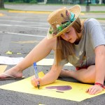 Sophomore Sadie McDonald writes a sign for the sophomores to hold during the parade. Photo by Bella Wolfe