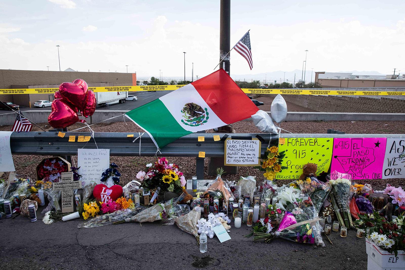 Una bandera de México destaca entre las flores, velas, fotos y peluches que fueron dejados en homenaje a las víctimas de la matanza en El Paso, Texas, frente a la tienda Walmart en donde ocurrió la tragedia. (LOLA GOMEZ/Austin American-Statesman/TNS)