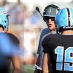 Coach Drew Steffen talks to the players after the opponents score a touch down. Photo by Trevor Paulus