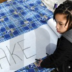 """Senior Kara Auvray looks to the side while making a """"bake sale"""" banner. Photo by Kate Nixon"""