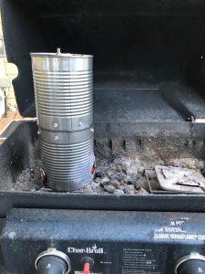 DIY Tin Can Smoker sitting inside a propane BBQ