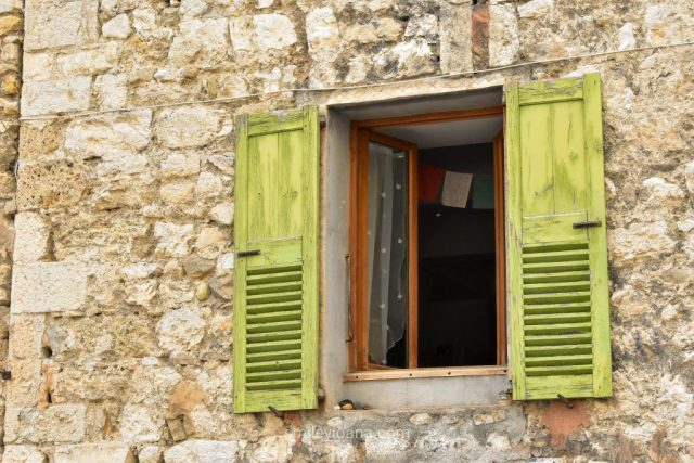 Castellane - windowCastellane - window with green wooden shutters and Nepalese lung ta flags with green wooden shutters