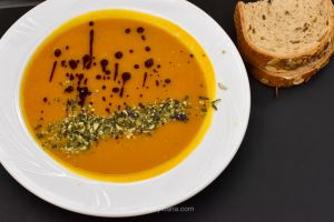 Pumpkin soup in a white plate served with pumpkin bread