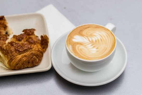 Latte and chocolate croissant from Ritual Coffee inside Flora Grubb Gardens