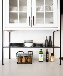 Glass-front cabinetry and open custom metal shelving in black and white kitchen