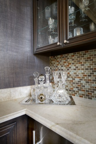 Crystal bar set on quartzite bar counter top with glass mosaic backsplash and metallic wallpaper