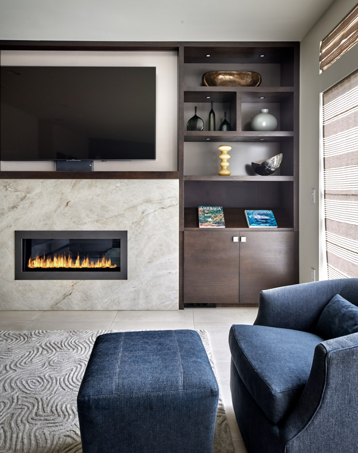 Blue swivel chair and ottoman in front of contemporary fire place with quartzite surround and patterned rug in family room