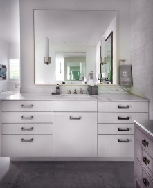 Organic master bath with white contemporary cabinets and sconces on mirror