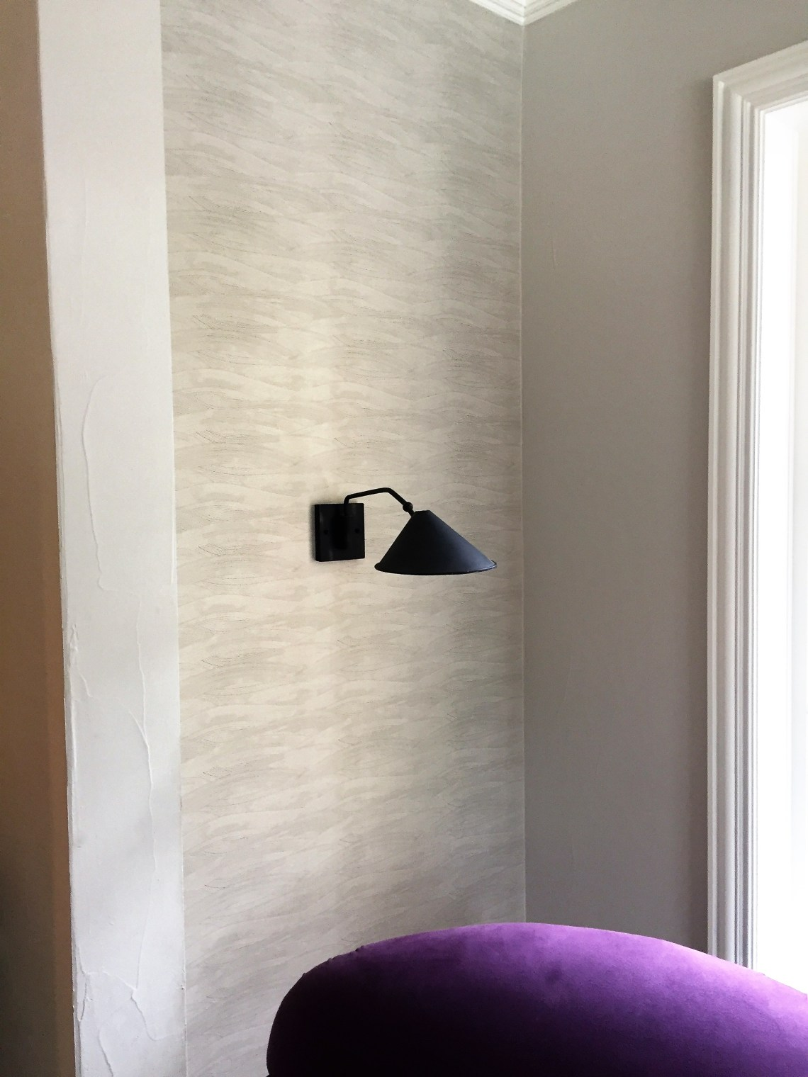single sconce on wall with wallpaper