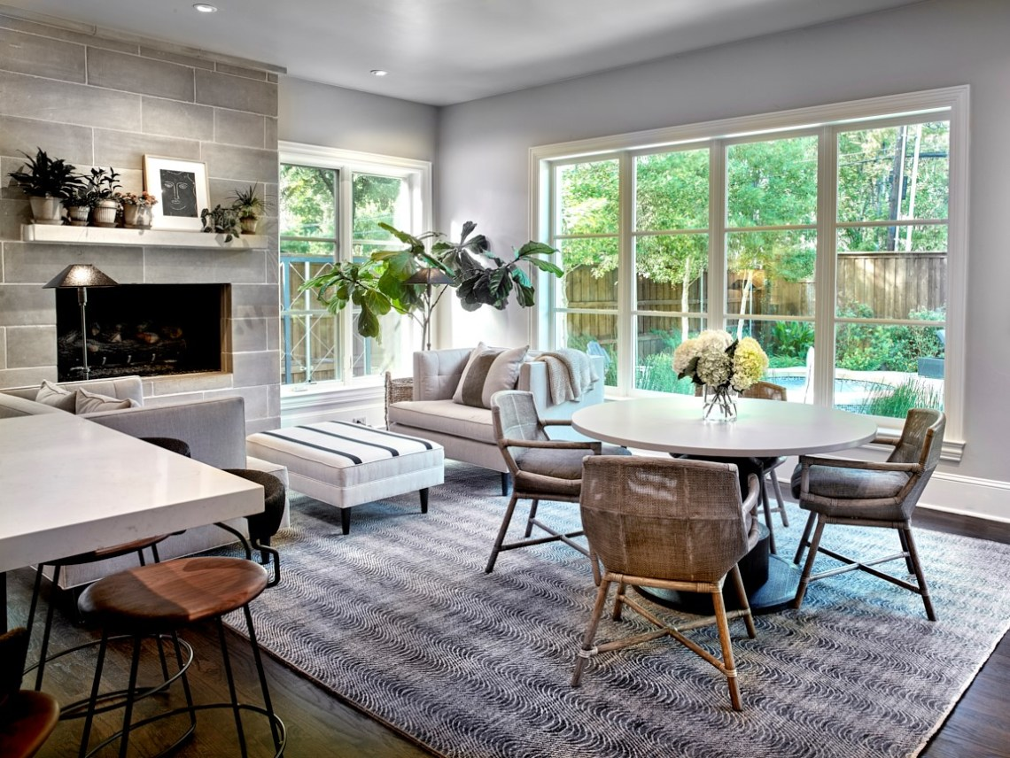 breakfast table and reading area in front of fire place with large windows