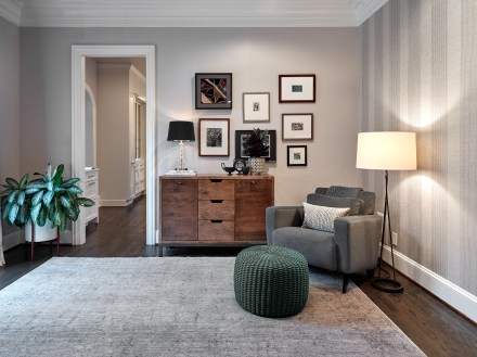 Gallery wall in study with gray chair and dark green pouf