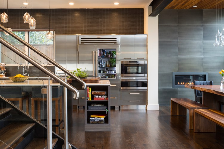 Stainless steel cabinetry with dark blacksplash and fireplace and live edge dining table