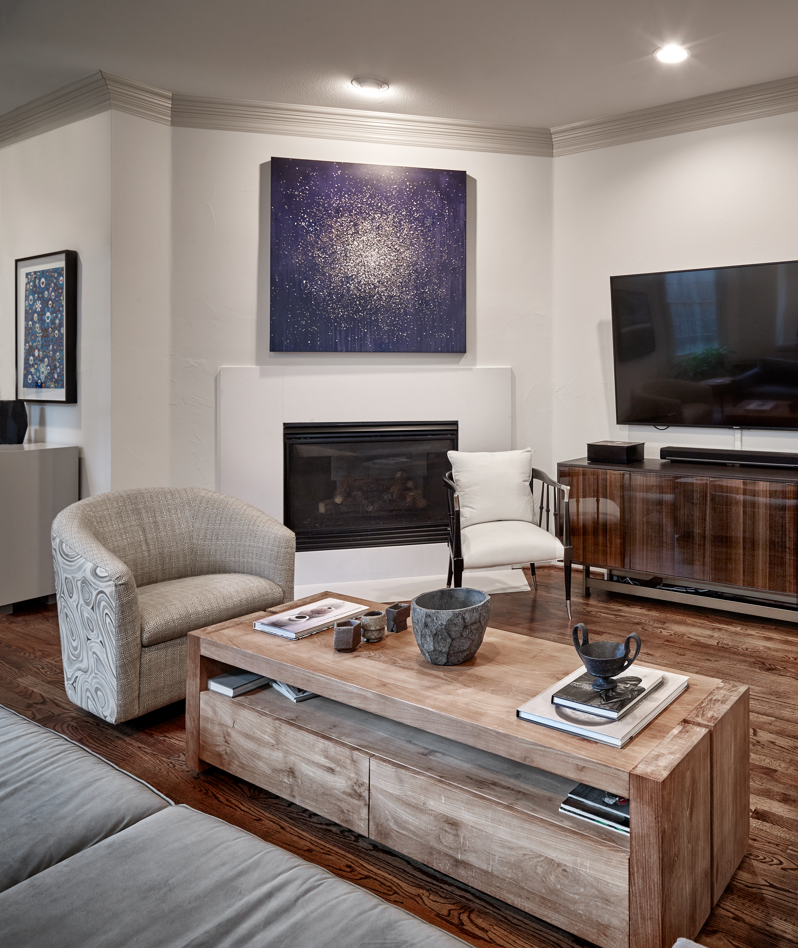 Blue art above contemporary fire place in living room