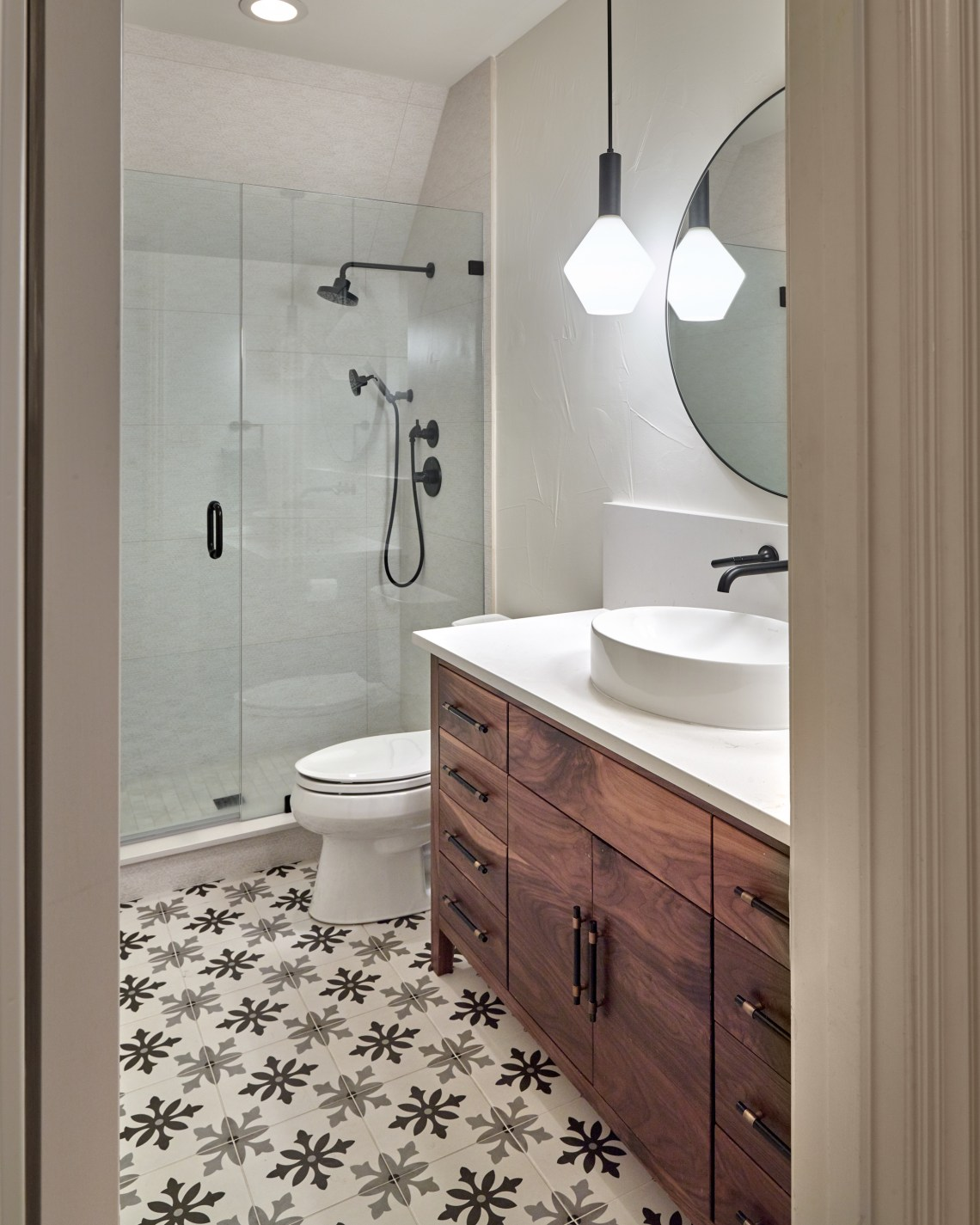 Bathroom with cement patterned tile floor and walnut vanity and vessel sink with black plumbing fixtures
