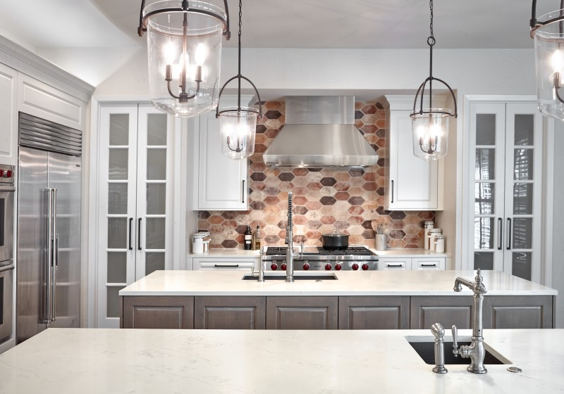 traditional white kitchen with wood island and hexagon brick backsplash