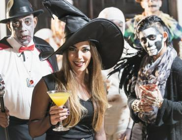 Three party-goers in Halloween costumes holding drinks