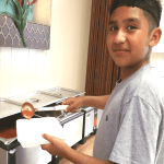 Abrian helps serve food with Meals on Wheels