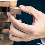 Man's hand manipulates building blocks.