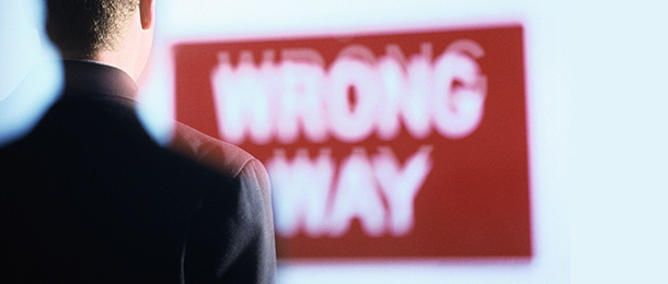 A red and white sign reading wrong way seen over shoulder of a man