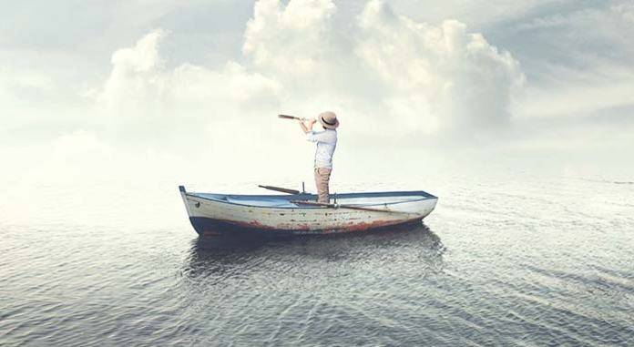 Man standing in small boat using telescope