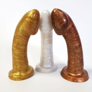 Three silicon dildos in the colors gold, silver and bronze.