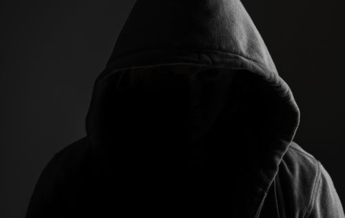 An image of someone wearing a hoodie but barely visible. Image is very dark.