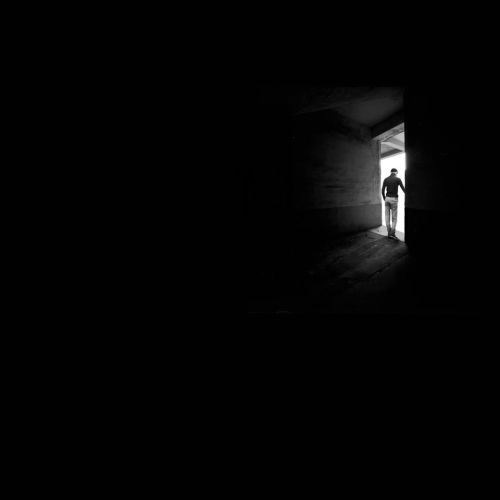 A black and white image showing mostly black and then an open door with a silhouette in he opening.