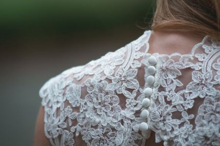 Back of woman's neck and shoulder with white lace wedding dress.